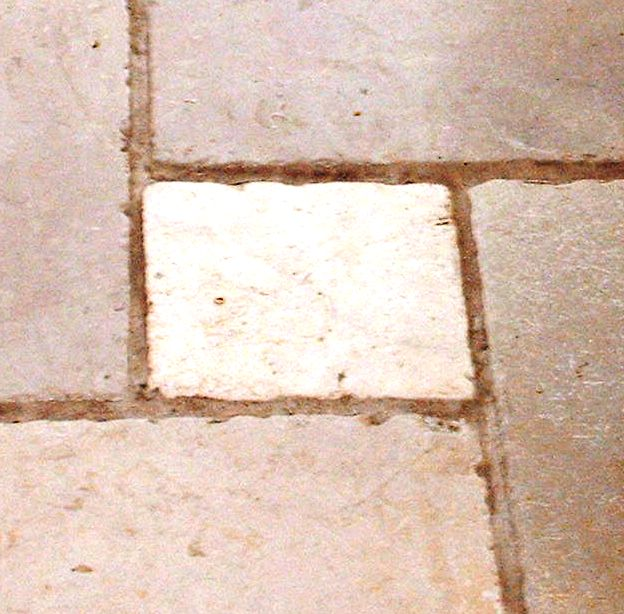 Mixed size marble floor tile with badly discoloured Ivory grout